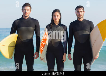 Group of friends in wetsuits with a surfboard on a sunny day - Stock Photo