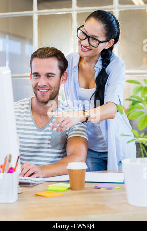 Smiling partners working together on computer - Stock Photo