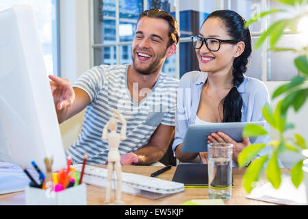Smiling partners working together on tablet and computer - Stock Photo