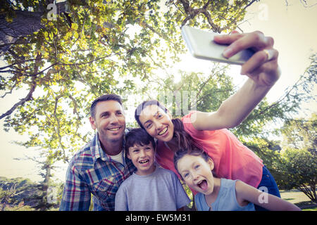 Happy family in the park taking selfie - Stockfoto