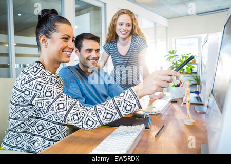 Smiling business team working together with computer - Stock Photo