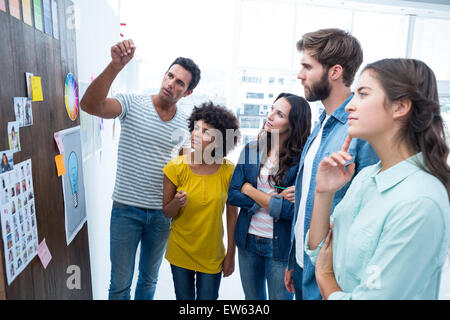 Creative business people at work by blackboard - Stock Photo