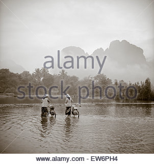 Two women wearing conical Asian hats push bicycles through a shallow river in Vang Vien, Laos. - Stock Photo