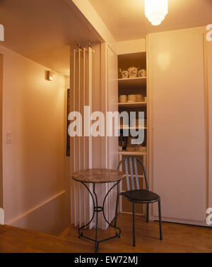 small dining table in front of a drinks cabi  in a
