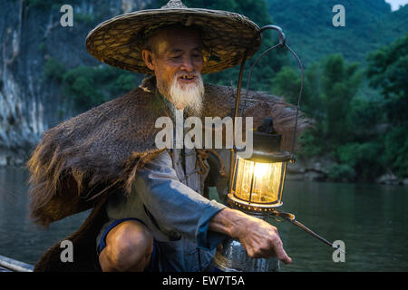 Portrait of an old chinese fisherman with lantern on bamboo boat - Stock Photo