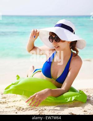 Teenage girl in a bikini sunbathing on the beach - Stock Photo