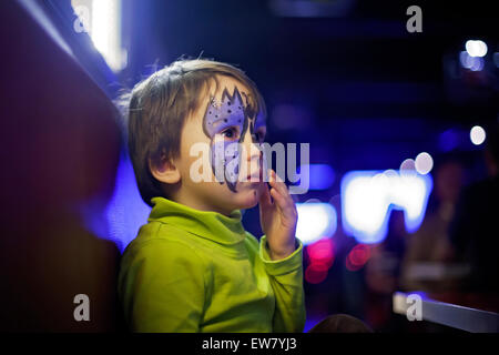 Little boy with painted face as butterfly, looking at the mirror in a restaurant - Stock Photo