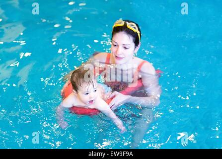 Little baby swimming in a pool with her mother - Stock Photo