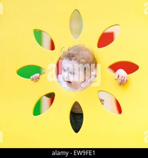 Funny curly baby girl playing hide and seek - Stock Photo