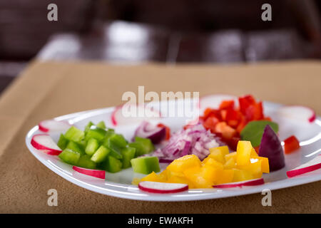 Fresh chopped vegetables on white plate for salad - Stock Photo