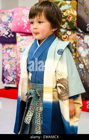3 to 5 year old Caucasian boy. Indoors. Standing dressed in Japanese kimono, facing, cute, angelic and wide eyed. - Stock Photo
