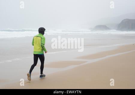 Runner man running on the beach in a rainy day - Stock Photo