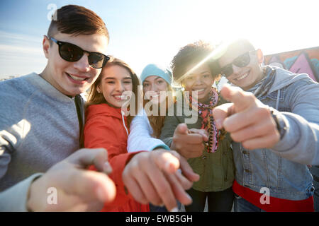 happy teenage friends pointing fingers on street - Stock Photo