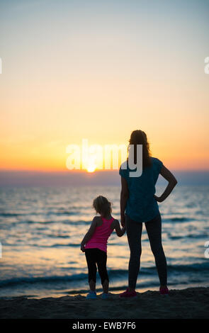 A mother and young daughter hold hands, silently looking out as the sun disappears into the sea on the horizon. - Stock Photo
