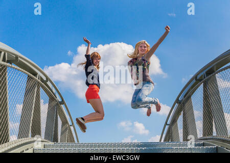 Two happy and enthusiastic teenage girls jumping on bridge in front of blue sky - Stock Photo
