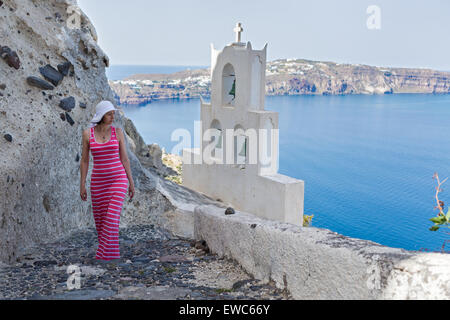 Woman walks up the mountain stairs, at the bottom of the bell tower of the Church. Greece Santorini - Stock Photo