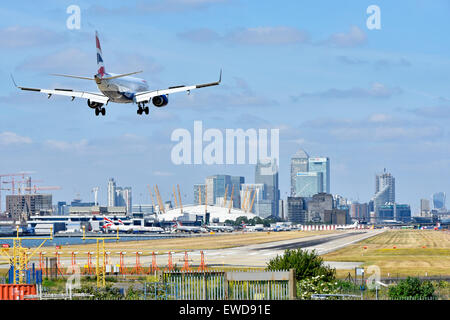 British Airways flight landing at London City Airport (Newham) with O2 arena and Canary Wharf (Tower Hamlets) skyline - Stock Photo