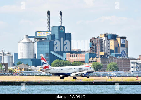 British Airways flight landing at London City Airport with Tate and Lyle sugar refinery factory buildings beyond - Stock Photo