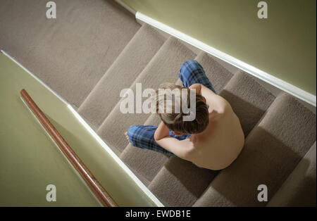 A child sitting on the stairs with his head in his hands looking upset - Stock Photo
