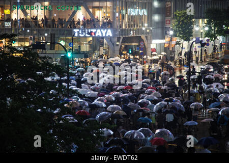 Shibuya Crossing at night in the rain in Tokyo, Japan - Stock Photo