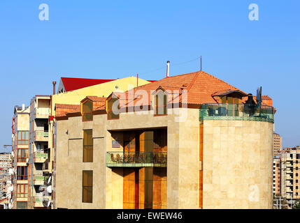 House with red roof and balconies on the background of blue sky - Stock Photo