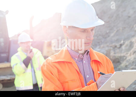 Engineer writing on clipboard at construction site with colleague in background - Stock Photo