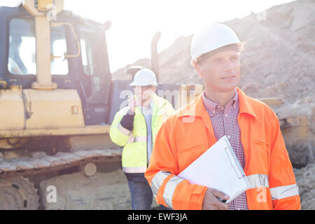 Engineer holding clipboard on construction site with colleague in background - Stock Photo