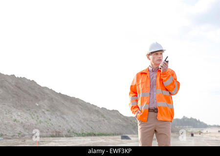 Confident male supervisor using walkie-talkie on construction site against clear sky - Stock Photo