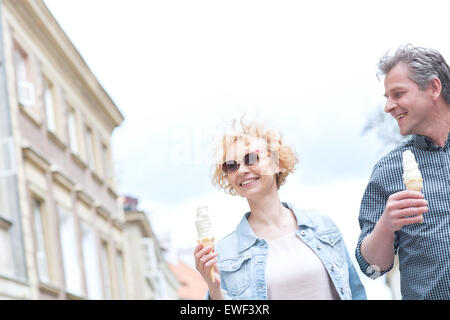 Smiling middle-aged couple holding ice cream cones on sunny day - Stock Photo