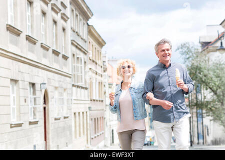 Happy middle-aged couple holding ice cream cones while walking in city - Stock Photo