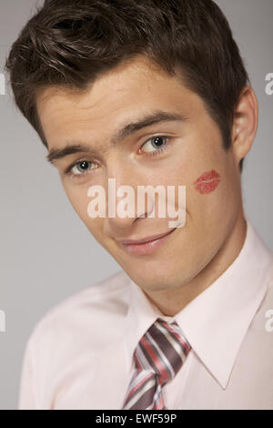Young caucasian businessman with lipstick kiss mark on his cheek - Stock Photo