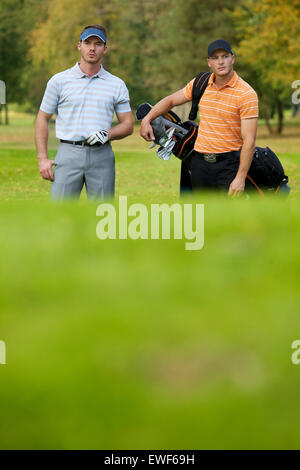 Young men standing on golf course carrying bags - Stockfoto