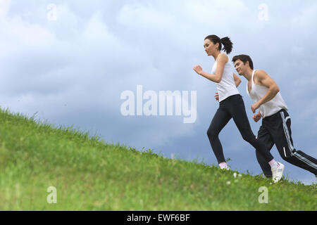 Young couple exercising in park - Stock Photo