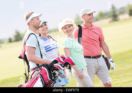 Happy friends walking at golf course - Stock Photo