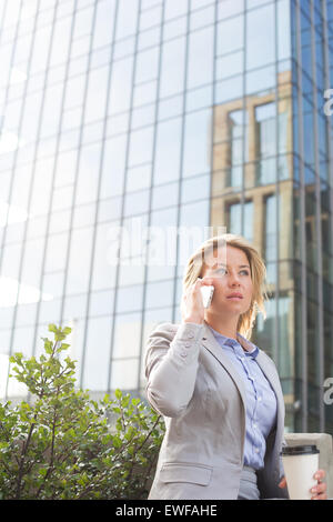Businesswoman using mobile phone outside office building - Stock Photo
