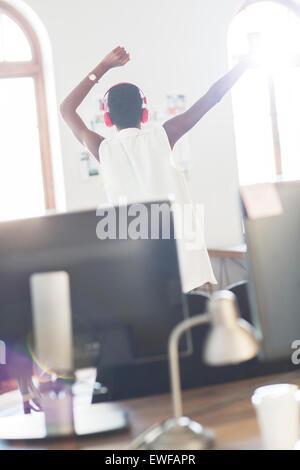 Casual businesswoman wearing headphones dancing in office - Stock Photo