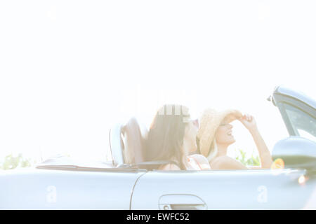 Happy female friends enjoying road trip in convertible on sunny day - Stock Photo