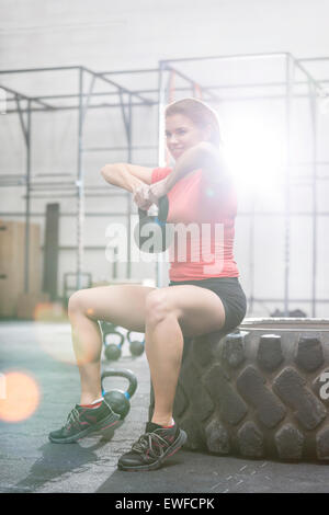 Smiling woman lifting kettlebell while sitting on tire at crossfit gym - Stock Photo