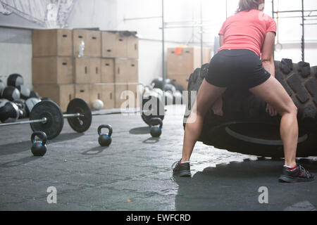 Rear view of woman flipping tire in crossfit gym - Stock Photo