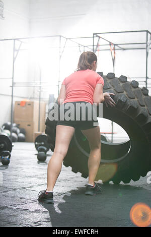 Rear view of woman flipping tire in gym - Stock Photo