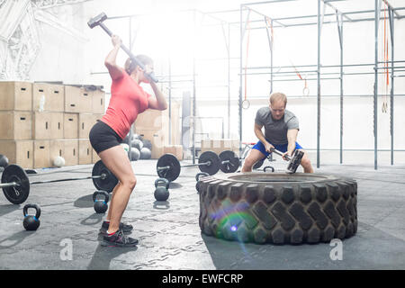 Dedicated man and woman hitting tire with sledgehammer in crossfit gym - Stock Photo
