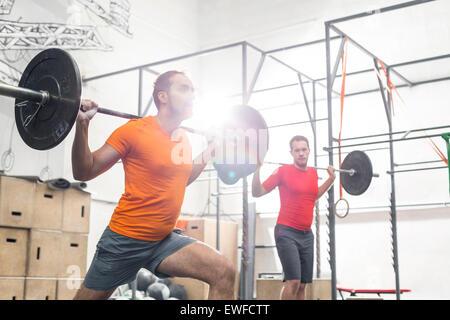 Men lifting barbells in crossfit gym - Stock Photo