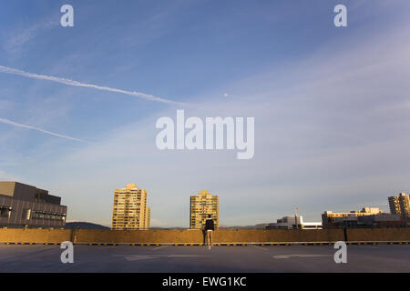 Person Standing on Top Floor of Parking Garage Clouds Human Parking Garage buildings person sky standing - Stock Photo