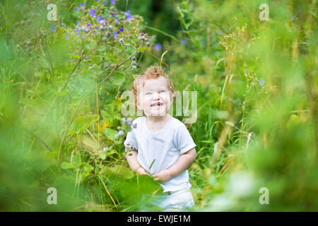 Funny laughing baby in a green summer field - Stock Photo