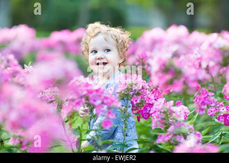 Portrait of a beautiful curly baby girl with blue eyes in a field of pink flowers - Stock Photo