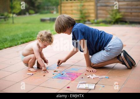 Brother and his baby sister playing together in the backyard painting with colorful chalk - Stock Photo