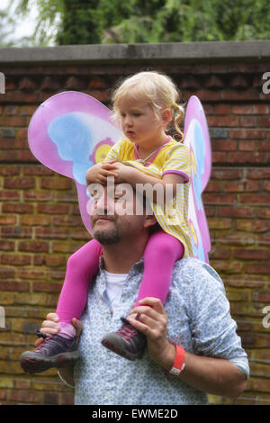 June 28, 2015 - Old Westbury, New York, United States - A young girl, dressed in a fairy costume, sits on shoulders - Stock Photo