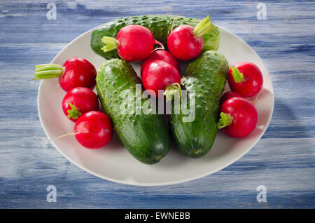 Fresh healthy   radish and cucumbers on a white plate. - Stock Photo