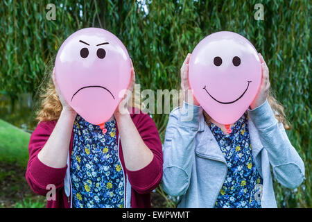 Two teenage girls holding balloons with smiling and angry facial expressions outdoors - Stock Photo