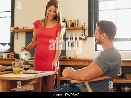 http://n450v.alamy.com/450v/ewr8ae/indoor-shot-of-couple-having-breakfast-in-kitchen-young-woman-pouring-ewr8ae.jpg